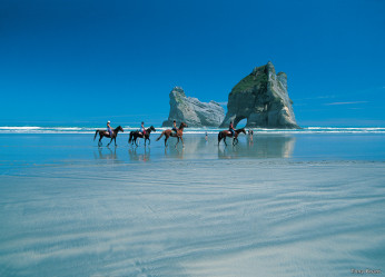 Horses and riders on Wharariki Beach in the Nelson-Tasman region of the South Island of New Zealand